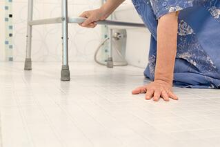 Woman with Walker on Floor in Bathroom