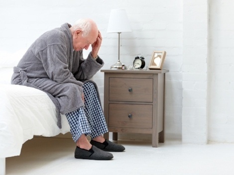 Distressed man getting out of bed