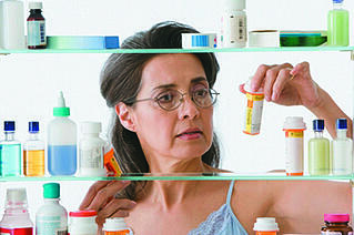 Adult woman checking her medicine cabinet
