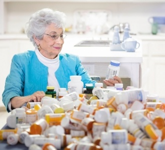 Elderly woman examining bottles of medication